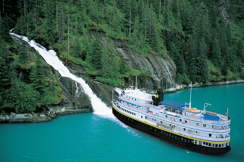 Uncruise ship - SS Legacy next to a waterfall.
