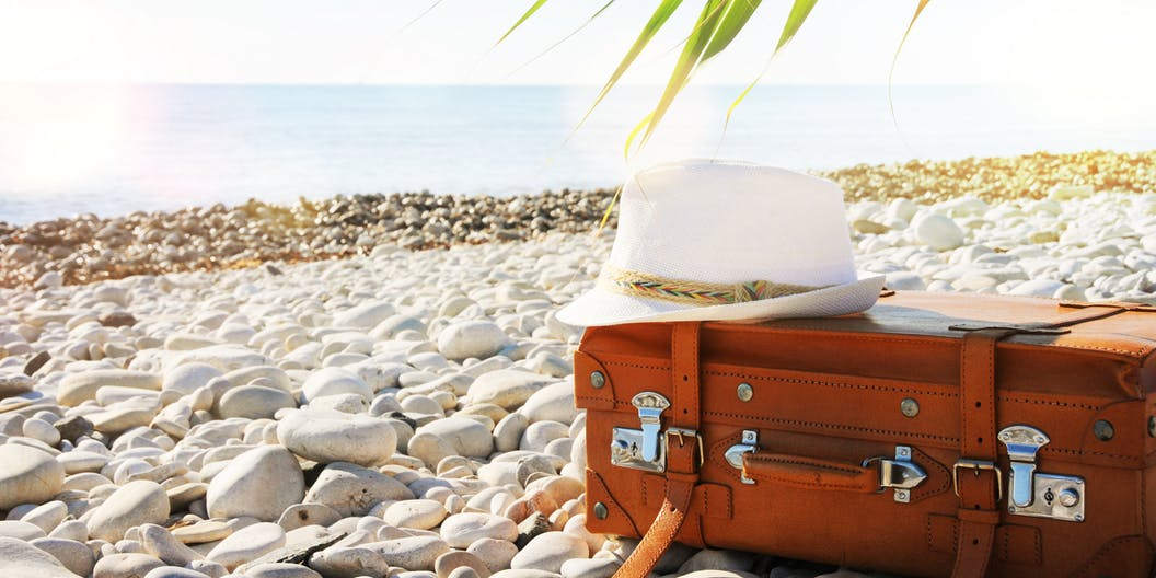 Suitcase and hat on the beach