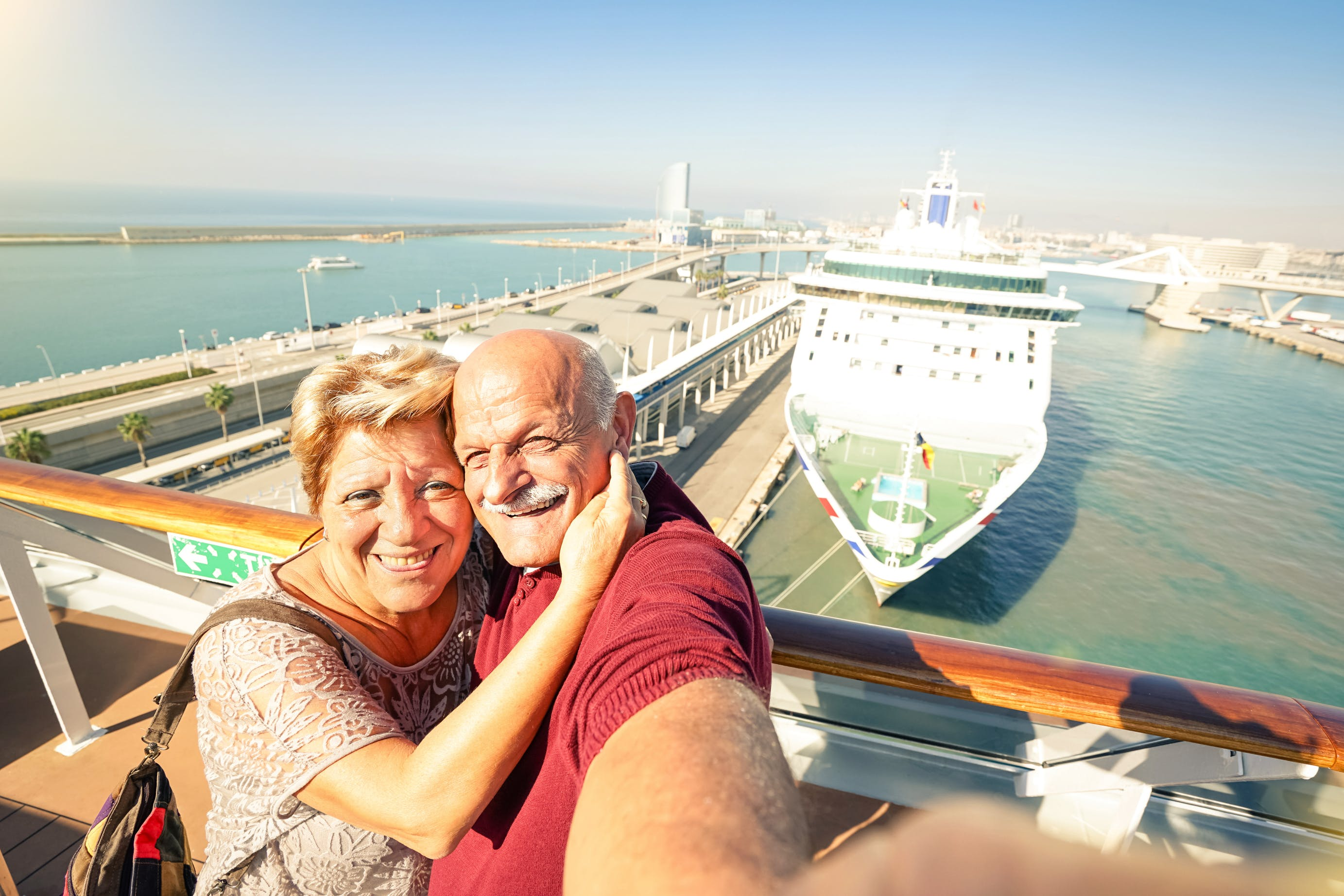 Senior couple taking selfie in front of cruise ship.